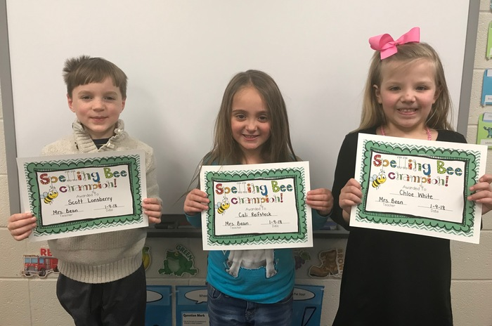 3 kids holding spelling bee certificates