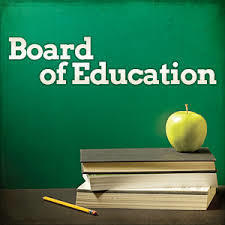 board of education written on a chalkboard with a green apple on three books with a pencil next to the books